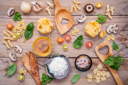 Italian foods concept and menu design. Fettuccine with wooden spatula and ingredients sweet basil ,tomato ,garlic ,parsley ,champignon and extra virgin olive oil setup on wooden background.