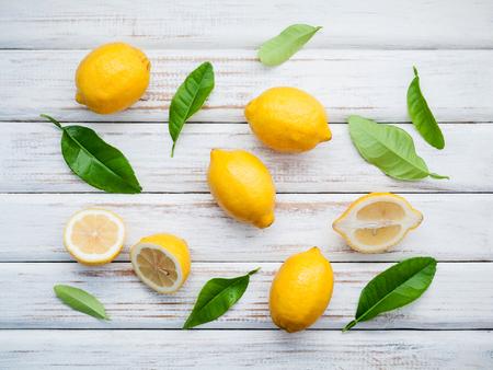 Fresh lemons and  lemons leaves on rustic wooden background. Fresh lemons and lemon slice on wooden table with flat lay.  Fresh citrus fruit background. Stock Photo