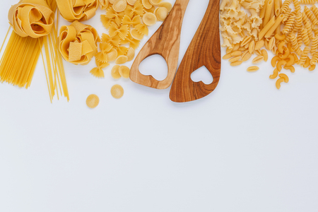 Italian foods concept and menu design. Various kind of Pasta Farfalle, Pasta A Riso, Orecchiette Pugliesi, Gnocco Sardo and Farfalle with wooden spatula setup on white wooden background with flat lay.