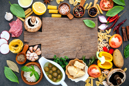 Italian food cooking ingredients on dark stone background with cutting board flat lay and copy space.