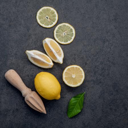 Fresh lemons and  lemons leaves on dark stone background. Fresh lemons and lemon slice on dark stone with flat lay.  Fresh citrus fruit background.