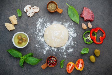 Raw dough for homemade pizza with with ingredients and herbs  flat lay on dark stone background.