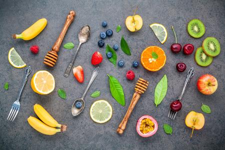 Plat leggen verschillende soorten vers fruit framboos, bosbes, aardbei, sinaasappel, banaan, passievrucht, appel en kersen setup op donkere stenen achtergrond. Zomer en zoet menu concept.