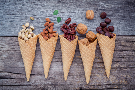 Concept for homemade various nuts ice cream. Mixed nuts in waffle cones on shabby wooden background.top view