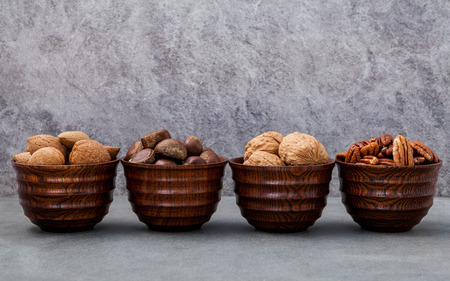 Whole almonds,whole walnuts ,whole hazelnut and pecan nuts in wooden bowl setup with stone background.  Selective focus depth of field.