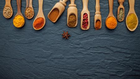 インドのスパイスと木製のスプーンでハーブの様々 な。フラットは、スパイス成分トウガラシ、コショウ、ニンニクのレイアウト、タイム、シナモ