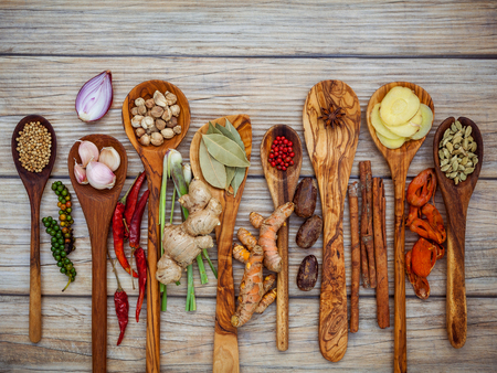 スパイスと木製のスプーンでハーブの様々 な。フラット レイアウト スパイス成分唐辛子、唐辛子トウモロコシ、ニンニク、タイム、オレガノ、シ 写真素材