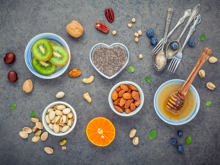 Ingredients for a healthy foods background, nuts, honey, berries, fruits, blueberry, orange, almonds, walnuts and chia seeds .The concept of healthy food set up on dark stone background. Flat lay . Stock Photo