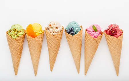アイスクリームの様々 な味のコーン ブルーベリー、ストロベリー、ピスタチオ、白い木製の背景にアーモンド、オレンジ、チェリーのセットアップ 写真素材