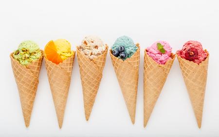 Divers de saveur de crème glacée dans les cornets de myrtille, fraise, pistache, amande, orange et cerise mis en place sur un fond en bois blanc. Concept de menu été et Sweet. Banque d'images - 86575645