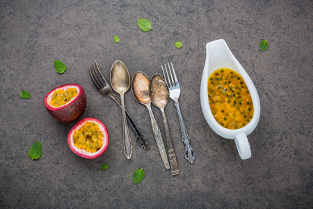 Fresh passion fruits set up on dark stone background. Passion fruits and juice with pepper mint leaves. Healthy food background concept.