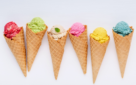 Various of ice cream flavor in cones blueberry ,strawberry ,pistachio ,almond ,orange and cherry setup on white wooden background . Summer and Sweet menu concept. Stock Photo