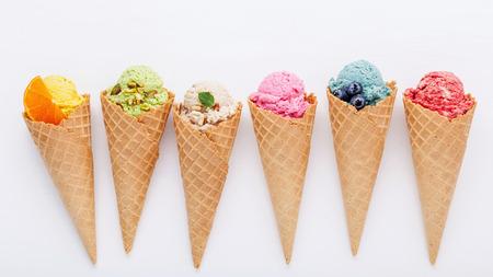 Divers de saveur de crème glacée dans les cornets de myrtille, fraise, pistache, amande, orange et cerise mis en place sur un fond en bois blanc. Concept de menu été et Sweet. Banque d'images - 86521210