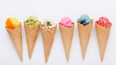 Various of ice cream flavor in cones blueberry ,strawberry ,pistachio ,almond ,orange and cherry setup on white wooden background . Summer and Sweet menu concept. Archivio Fotografico
