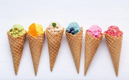 다양 한 아이스크림 맛 콘에서 블루 베리, 딸기, 피스타치오, 아몬드, 오렌지와 흰색 나무 배경에 체리 설치. 여름 및 달콤한 메뉴 개념입니다.