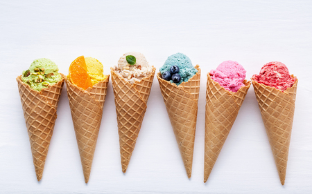 Various of ice cream flavor in cones blueberry ,strawberry ,pistachio ,almond ,orange and cherry setup on white wooden background . Summer and Sweet menu concept. Banque d'images