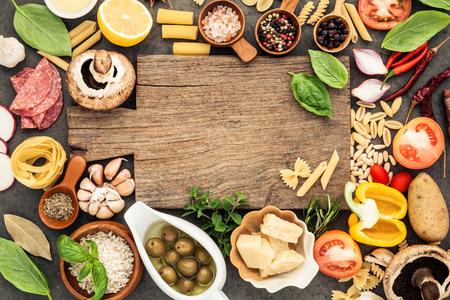 Italienisches Lebensmittel, das Bestandteile auf dunklem Steinhintergrund mit flachem Lay- und Kopienraum des Schneidebretts kocht.