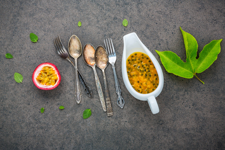 Fresh passion fruits set up on dark stone background. Passion fruits and juice with pepper mint leaves. Healthy food backgroud concept.