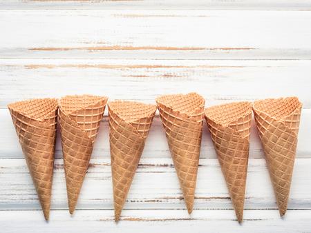 白い木製の背景にフラットレイアイスクリームコーンコレクション。お菓子のメニューデザインのためのコピースペース付きのブランククリスピー 写真素材
