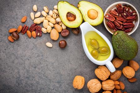 Ausgewählte Nahrungsquellen von Omega 3 und ungesättigten Fetten. Superfood High Vitamin E und Ballaststoffe für gesunde Ernährung. Mandel, Pekannuss, Haselnüsse, Walnüsse, Olivenöl, Fischöl und Lachs auf Steinhintergrund. Standard-Bild