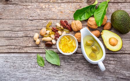 Ausgewählte Nahrungsquellen von Omega 3 und ungesättigten Fetten. Superfood High Vitamin E und Ballaststoffe für gesunde Ernährung. Mandel, Pekannuss, Haselnüsse, Walnüsse, Olivenöl, Fischöl und Lachs auf hölzernem Hintergrund.