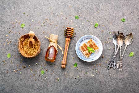 어두운 돌 배경에 원시 유기농 꿀벌 꽃가루. 꿀벌 꽃가루 알갱이 및 코코넛 껍질에 프로 폴리스. 꿀벌 꽃가루와 박하와 백 리 향 플랫 누워 동종 요법