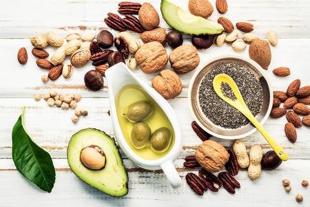 Auswahl der Nahrungsquellen für Omega-3-Fettsäuren und ungesättigte Fette. Superfood, hohes Vitamin E und Ballaststoffe für gesundes Essen. Mandel, Pekannuss, Haselnüsse, Walnüsse und Olivenöl auf Steinhintergrund.