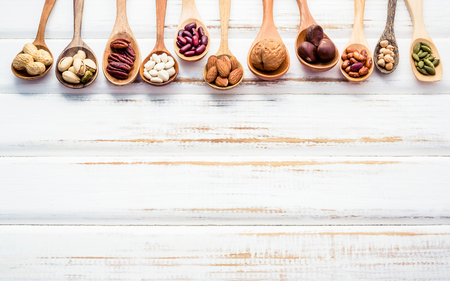 Selection food sources of omega 3 and unsaturated fats. Superfood high vitamin e and dietary fiber for healthy food. Mixed nuts almond ,pecan,hazelnuts,walnuts and various beans on white background. Banco de Imagens