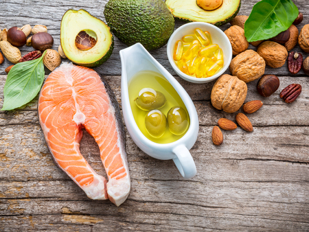 Selection food sources of omega 3 and unsaturated fats. Superfood high vitamin e and dietary fiber for healthy food. Almond,pecan,hazelnuts,walnuts,olive oil,fish oil and salmon on wooden background. Archivio Fotografico