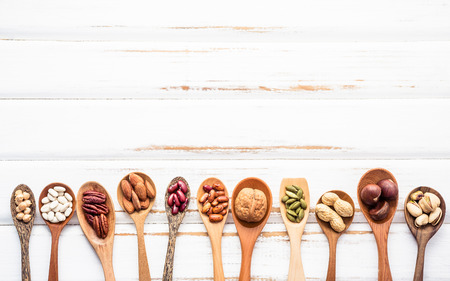 Selection food sources of omega 3 and unsaturated fats. Superfood high vitamin e and dietary fiber for healthy food. Mixed nuts almond ,pecan,hazelnuts,walnuts and various beans on white background. Archivio Fotografico
