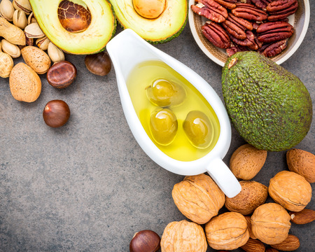 Selection food sources of omega 3 and unsaturated fats. Superfood high vitamin e and dietary fiber for healthy food. Almond ,pecan,hazelnuts,walnuts,olive oil,fish oil and salmon on stone background.