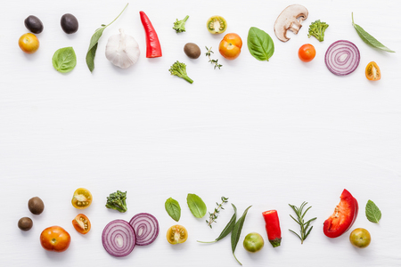 Various fresh vegetables and herbs on white background.Ingredients for cooking concept sweet basil ,tomato ,garlic ,pepper and onion with flat lay. Stock Photo