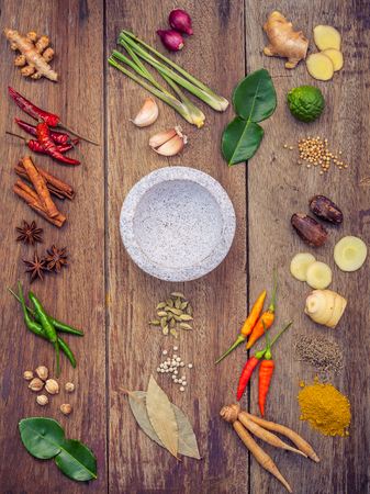 Various of Thai food Cooking ingredients and spice red curry paste ingredient of thai popular food on rustic wooden background. Spices ingredients chilli ,pepper, garlic and Kaffir lime leaves . Banco de Imagens