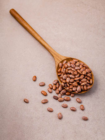 The composition of raw pinto beans in wooden spoon on brown background. Stock Photo