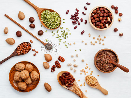 Various legumes and different kinds of nuts walnuts kernels ,hazelnuts, almond kernels,brown pinto ,soy beans ,flax seeds ,chia ,red kidney beans and pecan set up on white wooden table. 스톡 콘텐츠