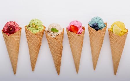 Varios de sabor de helado en conos de arándano, fresa, pistacho, almendra, naranja y cereza sobre fondo blanco de madera