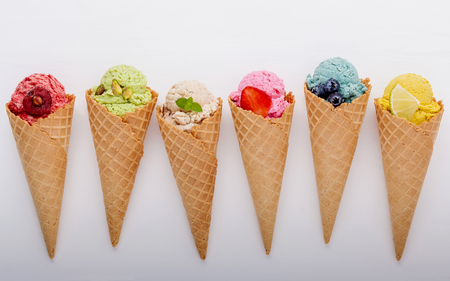 Various of ice cream flavor in cones blueberry ,strawberry ,pistachio ,almond ,orange and cherry setup on white wooden background Imagens