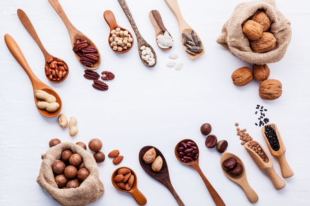 Hemp Sack bags and spoon of various legumes and different kinds of nuts walnuts kernels ,hazelnuts, almond kernels,brown pinto ,red kidney beans and pecan set up on white wooden table.