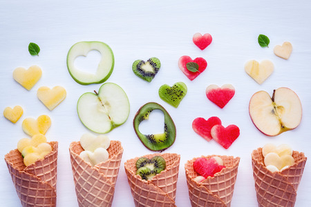 Various fruits in waffle cones and heart shape of fruits setup on white wooden background