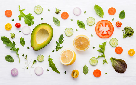 Food pattern with raw ingredients of salad, lettuce leaves, cucumbers, tomatoes, carrots, broccoli, basil ,onion and lemon flat lay on white wooden background. Stock Photo