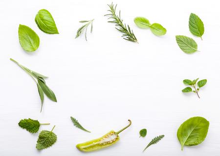 Varias hierbas frescas para cocinar ingredientes de menta, albahaca dulce, romero, orégano, salvia y tomillo de limón sobre fondo blanco de madera con espacio plano y copia.