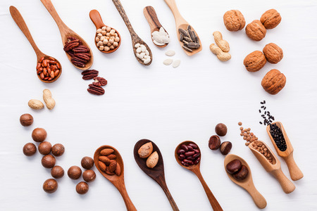 Spoon of various legumes and different kinds of nuts walnuts kernels ,hazelnuts, macadamia ,almond kernels,brown pinto ,red kidney beans and pecan set up on white wooden table.