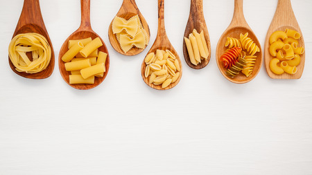 Various kind of Pasta Farfalle, Pasta A Riso, Orecchiette Pugliesi, Gnocco Sardo and Farfalle in wooden spoons setup on white wooden background with flat lay.