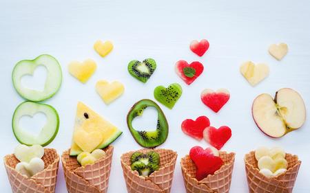 Divers fruits dans des cônes de gaufre et forme de coeur de la fibre de fruit sur fond blanc bois Banque d'images - 99063563