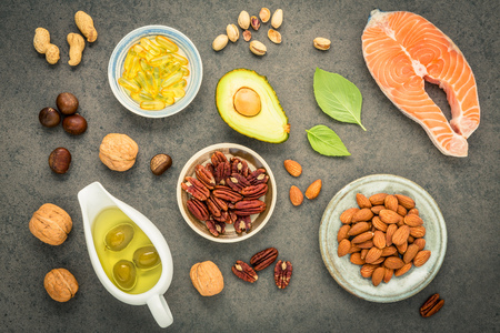 Almond ,pecan,hazelnuts,walnuts,olive oil,fish oil and salmon on stone background.
