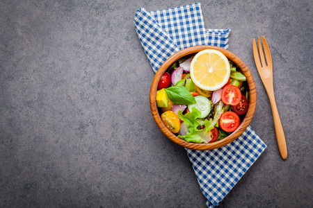 The bowl of healthy vegan salad . Various vegetables avocado, tomato, cucumber, red cabbage, basil and onion on dark stone background . Stock Photo