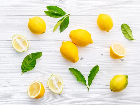 Fresh lemons and  lemons leaves on white wooden background. Stock Photo