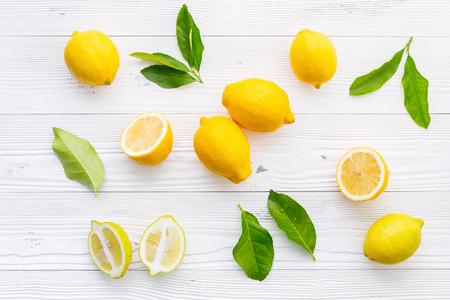 Fresh lemons and  lemons leaves on white wooden background. Imagens