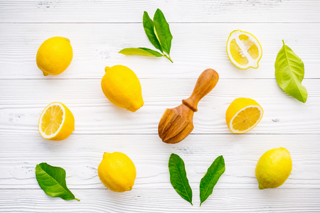 Fresh lemons and  lemons leaves on white wooden background. 版權商用圖片
