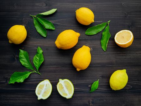 Fresh lemons and  lemons leaves on dark wooden background.